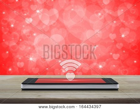 Heart wifi icon on modern smart phone screen on wooden table over blur red background Internet online love connection Valentines day concept