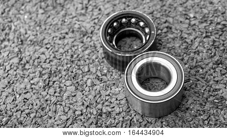 Car Suspension and car bearing parts concept - New wheels car bearing and old wheels car bearing on asphalt floor in garage and copyspace