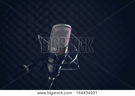 Microphone and audio console in holder, isolated on dark background in recording studio. Toned image