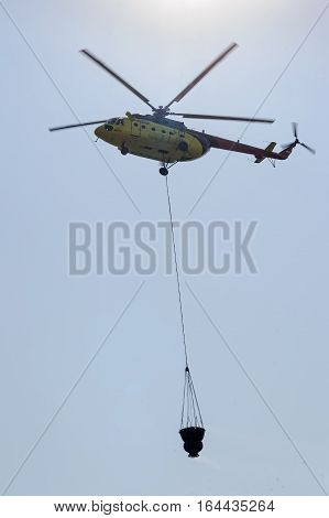 Tyumen, Russia - August 11, 2012: On a visit at UTair airshow in Plehanovo heliport. Cal-Fire helicopter gets ready to drop fire-fighting water bucket on woodland fire.