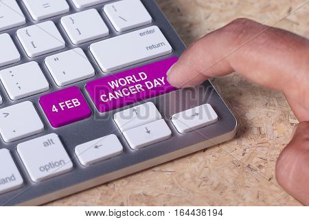 Man pressed keyboard button with world cancer day word