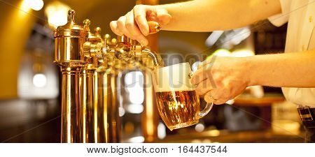 the gold beer in the hand and beer taps