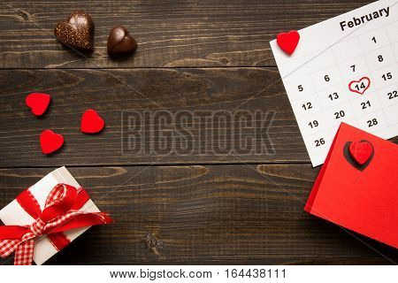 Valentine's day background with copy space. Valentine's Day card, gift box and chocolate on the wooden texture table.