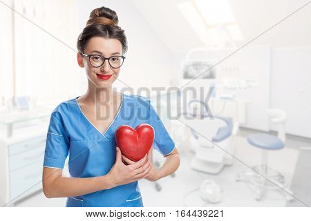 Portrait of female doctor with red heart in the dental office