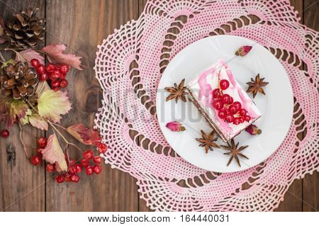 Cherry sponge cake with cream and red currant. Wooden background. Top view