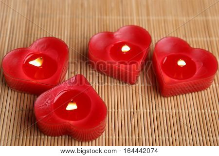 Heart shape candles. Four red candles burning.