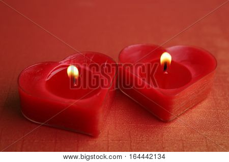 Heart shape candles. Two red candles burning.