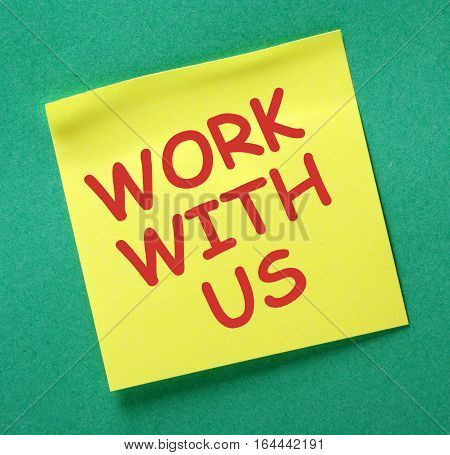The words Work With Us in red text on a yellow sticky note as an invitation to take up a job offer or engage in teamwork