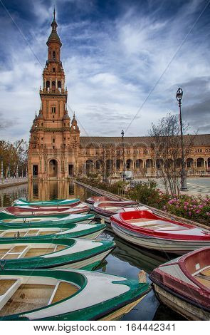 Boats docked at the canal with north tower at de bottom. Plaza de Espana in Seville Spain