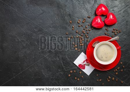 Red cup of coffee with hearts on stone table. Top view with copy space. Valentine's day background
