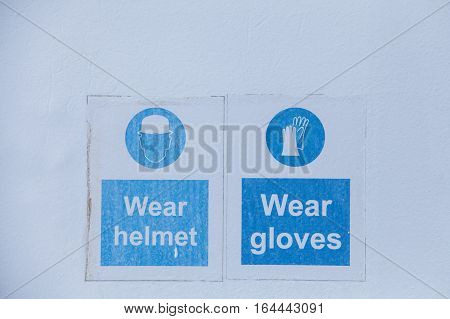 Close up shot of some signs with mandatory helmet and gloves.