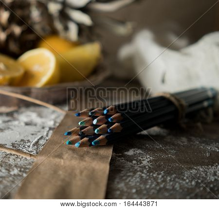set of pencils on a wooden table on a background of tropical fruit