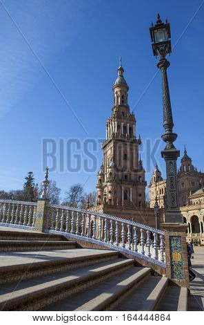Lamppost and tower beside one canal bridge at Plaza de Espana Seville Spain