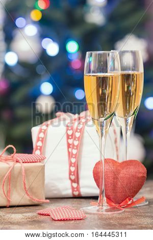 Valentine's Day still life with pair of Champagne flute glasses, gift box and red heart on bokeh background
