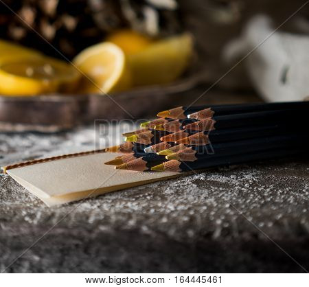 set of colored pencils on a wooden table on a background of tropical fruit