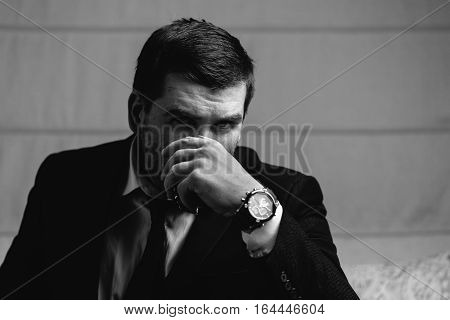Serious young businessman is drinking a glass of whiskey