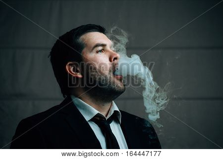 Young successful businessman exhales cigarette smoke white clubs