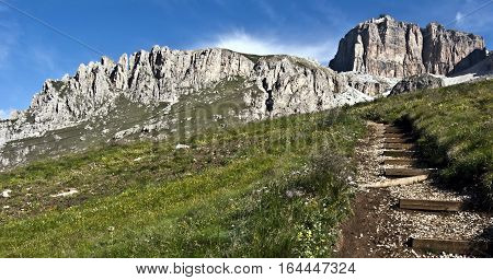 beautiful panorama of Piccolo Pordoi and Sass Pordoi with meadow and hiking trail bellow with blue sky during hiking from Passo Pordoi to Piz Boe peak in Dolomites
