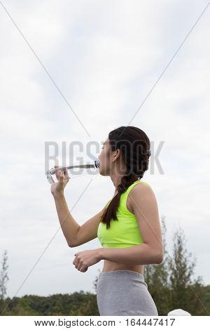 Sport And Health Lifestyle - Young Woman Drinking Water From A Bottle After Workout Exercising In Pa