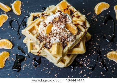 Photo of few Belgian wafers with chocolate, tangerines and ice-cream on blackboard
