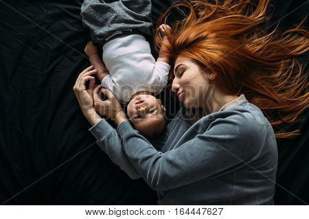 Happy mother with baby lying together on bed at home