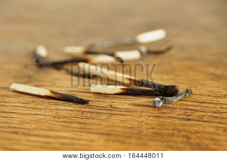 Heap of burnt matches on the wooden background as a symbol of exhaustion, depletion and destruction