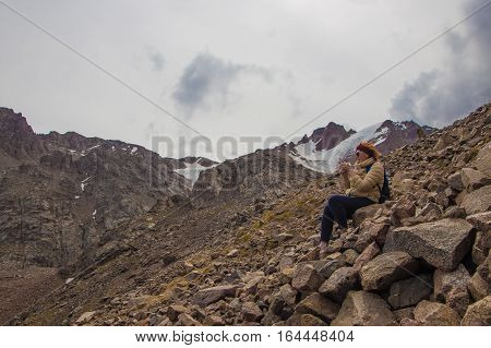 Aged sport woman in sunglasses are sitting on the rocks near the snow peak with glacier Tien Shan mountains Almaty Kazakhstan 2016