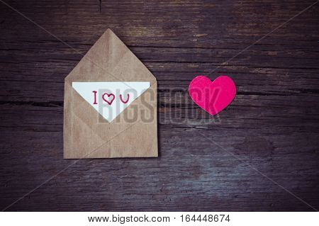 Envelope with card and text I love you and red hearts for valentine day on wooden table