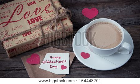 Note happy St. Valentine's Day with gift and cup of coffee on wooden
