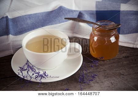 Green tea in a white cup and jar of honey with spoon and blue kitchen napkin on wooden background