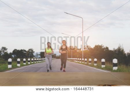Young Woman Running At The Park (blur Image) With Selected Focus Empty Wood Table For Display Your P