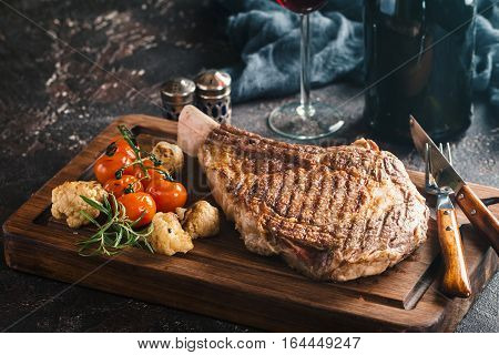 Succulent grilled tomahawk beef steak on the bone with red wine, seasonings, fresh rosemary and grilled vegetables on cutting board
