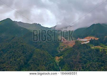 Mountain landscape: steep mountains covered with forests form a deep gorge in the distance you can see mountain ranges with clouds over the tops pouring rain in the mountains.