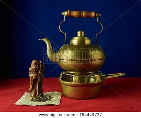 Still life with a statuette of the god tea green tea and the old non-ferrous metal teapot on a stand on a red background