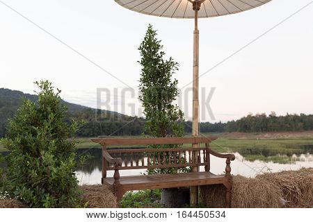 Wood Bench And Umbrella At Waterside Of Pond In Park