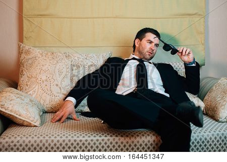 Young stylish businessman with sunglasses sitting on the couch
