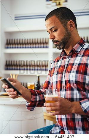 Portrait of handsome brunet man with beer using phone
