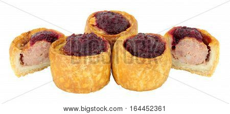 Cranberry sauce topped crusty mini pork pies isolated on a white background