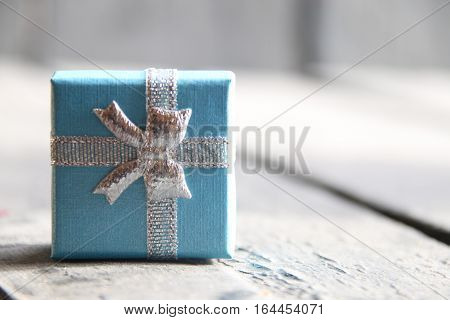 Gift box with ribbon on vintage wooden background