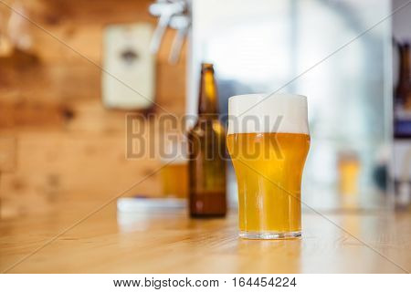 Glass of froth beer on table.Bottled beer on background