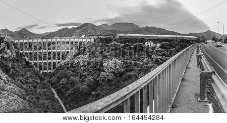 Aqueduct Puente del Aguila or Eagle Bridge in Nerja Malaga Spain. Panoramic from road beside