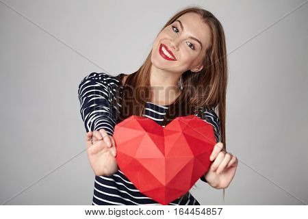 Playful emotional woman with red lips showing outstretching red polygonal paper heart shape