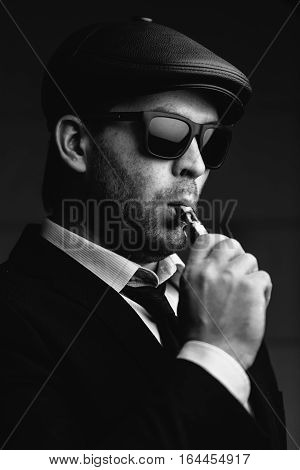 Fashionable man in sunglasses and a leather cap smokes an electronic cigarette. Black and white photography