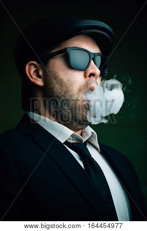 Fashionable man in sunglasses and a leather cap exhales clouds of white smoke