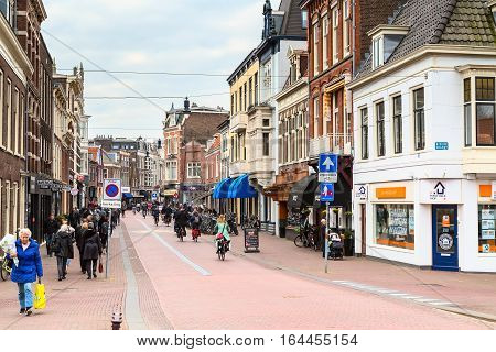 Haarlem, Netherlands - April 2, 2016: Street view with beautiful traditional houses, people in Haarlem, Holland