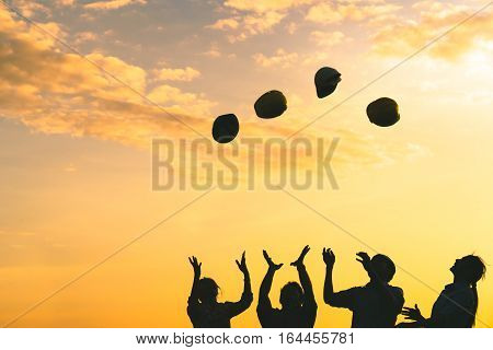 Silhoutte of construction engineers throwing safety helmets upward on golden sunset sky multiethnic diverse group engineering industry or success teamwork celebration concept
