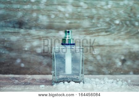snow bottle of perfume in wooden background