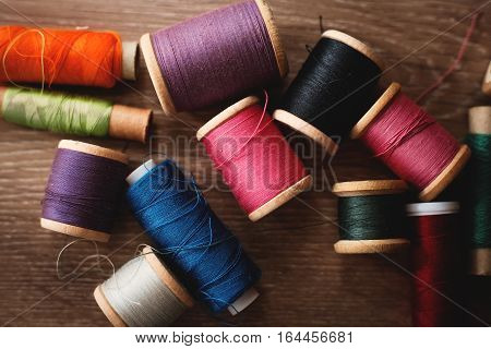 Colorful spools of thread in wooden background