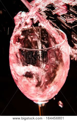Glass of red wine on dark background.
