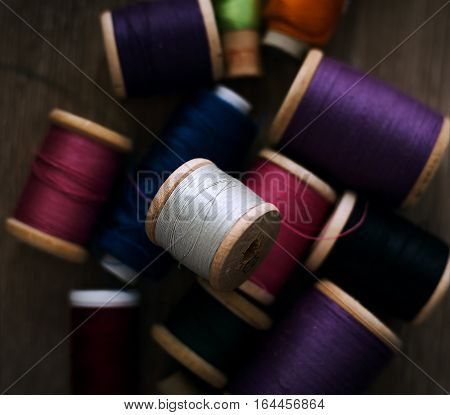 Colorful spools of thread in wooden Background.